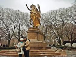 In the background is the majestic, gilded-bronze equestrian group statue which depicts one of the United States' best-known generals, William Tecumseh Sherman (1820 – 1891). Dedicated in 1903, it was master sculptor Augustus Saint-Gaudens's (1848 – 1907) last major work, and serves as the centerpiece of Manhattan's Grand Army Plaza. (http://www.nycgovparks.org/parks/grand-army-plaza-m062/monuments/1442)